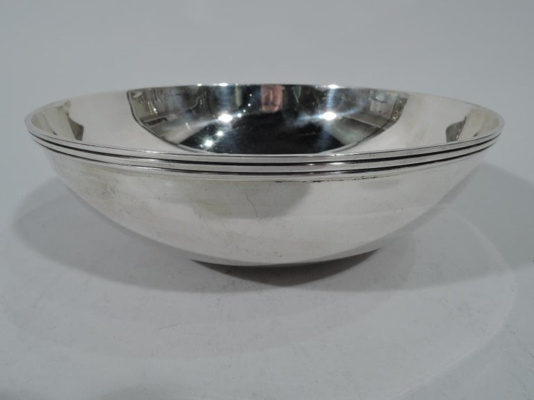 Mid-Century Modern sterling silver bowl. Made by Tiffany & Co. in New York. Circular well, curved sides, and reeded rim. Hallmark includes pattern no. 22843 and director's letter M (1947-56). Measures: Weight 12.5 troy ounces.