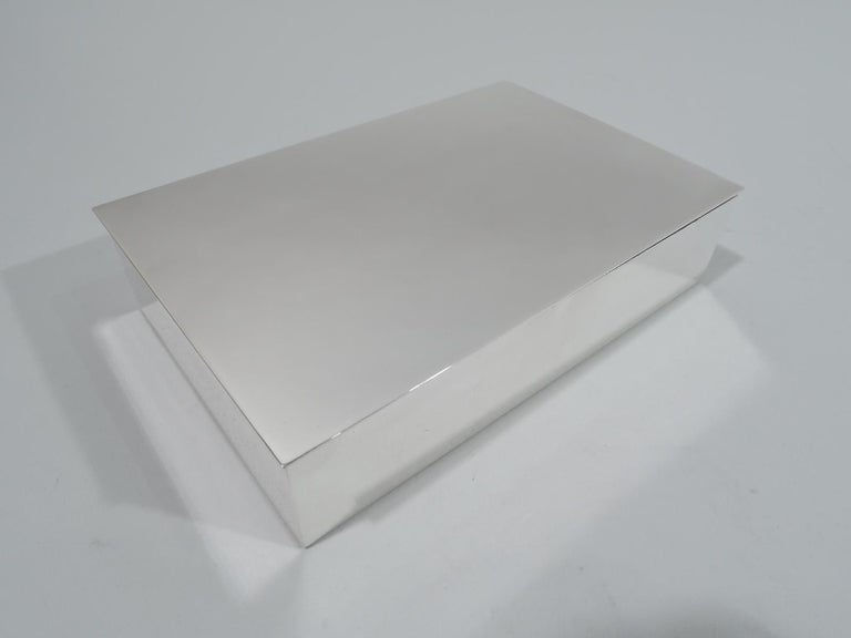 Mid-Century Modern sterling silver box. Made by Tiffany & Co. in New York. Rectangular with straight sides. Cover flat and hinged with slight overhang. Box interior cedar-lined and partitioned. Fully marked including postwar pattern no. 23705. Gross
