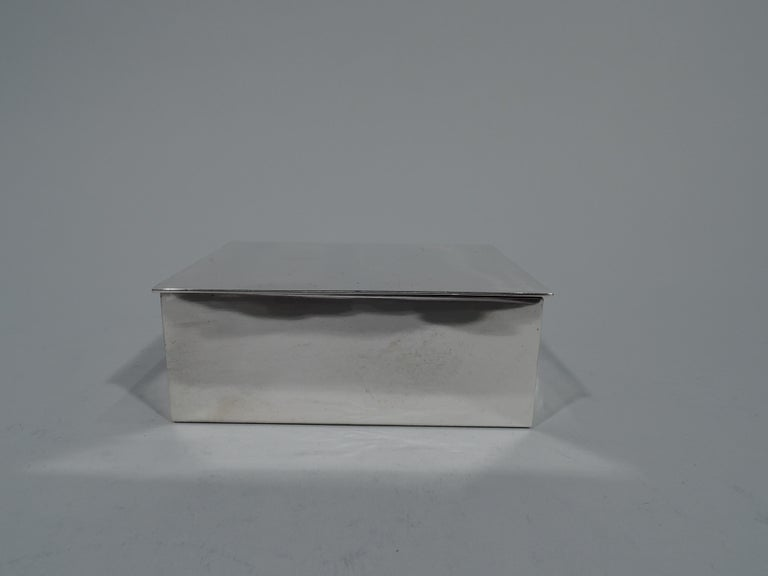 Modern and compact sterling silver box. Made by Tiffany & Co. in New York. Rectangular with flat, hinged, and overhanging cover. Box interior cedar lined. Hallmark includes postwar pattern no. 23325 and director's letter L (1956-circa 1965). Gross