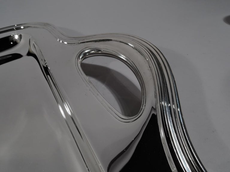 Modern sterling silver tea tray. Made by Tiffany & Co. in New York, circa 1908. Rectangular with curved corners and deep well. Molded rim and fluidly shaped ends with cutout lunette handles. Double sided beautiful including the elegant handle mounts