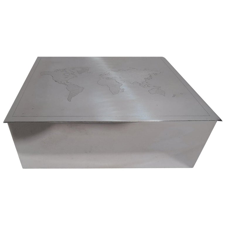 Modern sterling silver box. Retailed by Tiffany & Co. in New York. Rectangular with straight sides and flat and hinged cover. On cover is engraved map of world with linear shading. Box interior cedar lined. A great gift for someone who is going