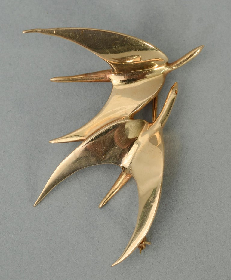 This Tiffany brooch depicting two birds in flight is the ultimate in Modernist abstraction and minimalism. Streamlined as it is, it very effectively conveys the movement of the pair. The brooch is 2 1/4 inches in width and 2 1/8 inches tall. It can