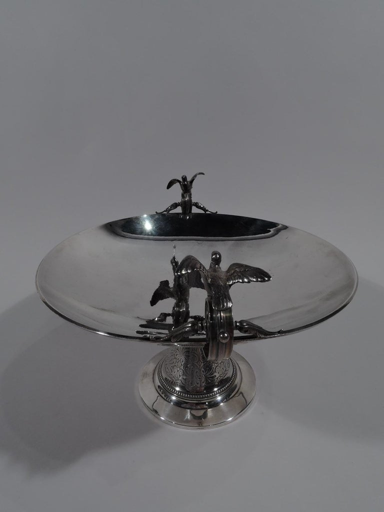 Aesthetic sterling silver compote. Retailed by Tiffany & Co. in New York, circa 1870. Shallow round bowl mounted to conical support on flat foot. A spare form suggestive of the Greek kylix with low and deep side handles terminating in volute scrolls