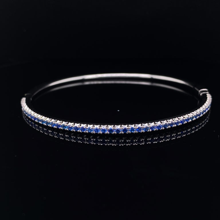 A Tiffany sapphire bangle in 18 karat white gold.  This slim elegant gold bangle bracelet has a hinged fitting and is claw set to its top half with rich, bright deep hued sapphires.  Its pared back design places all focus on the sapphires, allowing