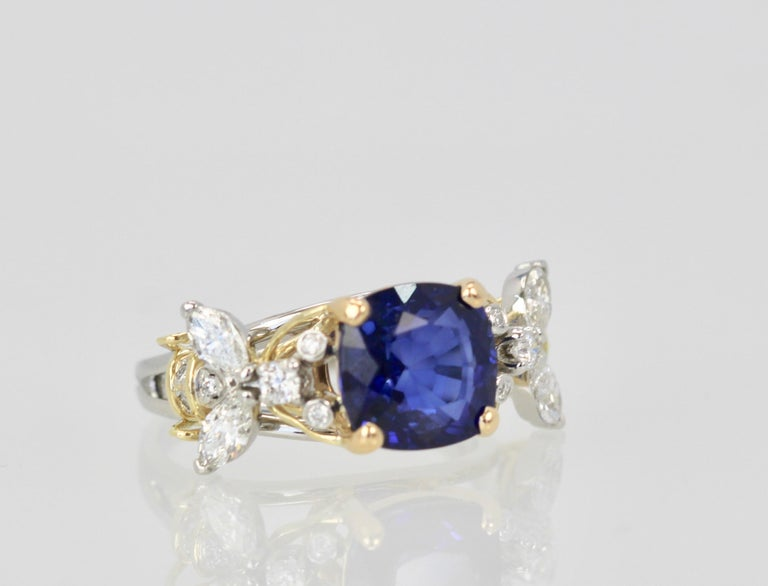 This Tiffany double bee ring with center Sapphire is highly coveted and hard to find.  This ring features a gorgeous Blue Sapphire of 4.39 Carats cushion cut w/ AGI certificate.  There are 4 marquise Diamonds weighting 0.60 carats, round brillant