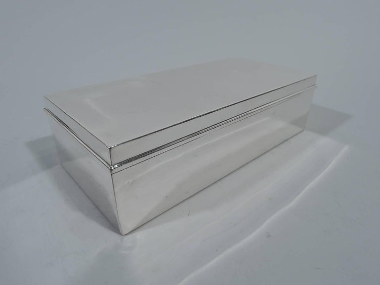 Smart and modern sterling silver desk box. Made by Tiffany & Co. in New York, circa 1936. Rectangular with straight sides and sharp corners. Cover hinged with molded rim. Box interior cedar lined. Hallmark includes pattern no. 22353 (first produced
