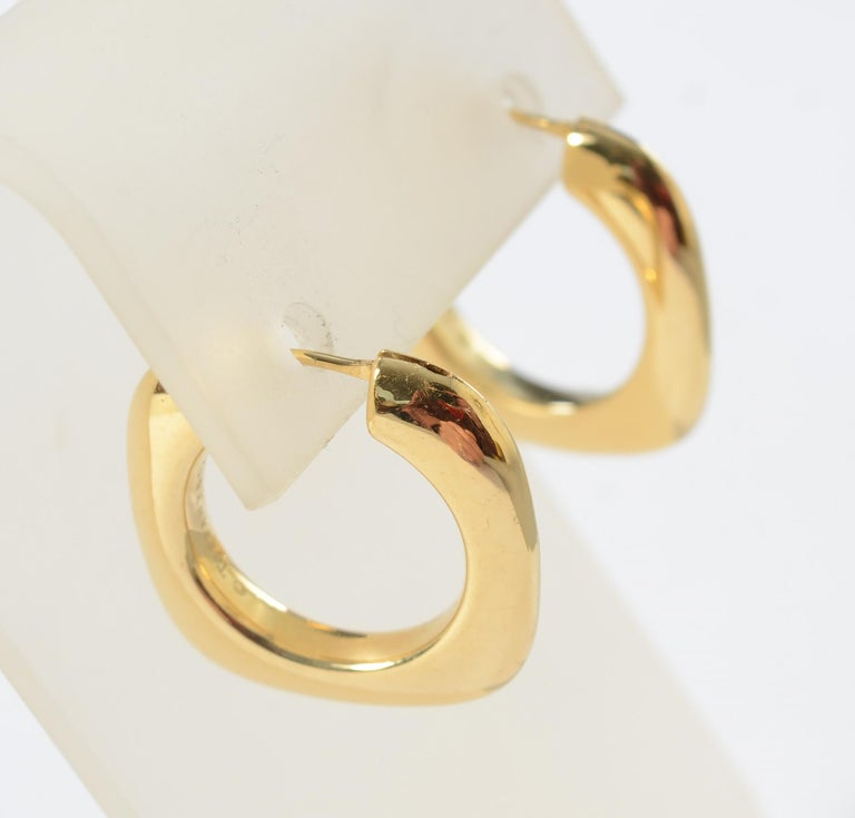 Square hoop earrings by Tiffany in 18 karat gold. The square exterior has rounded corners and a circular interior. The earrings match Modernist Tiffany bracelet listed as item LU13310742662. The earrings have posts for pierced ears.
