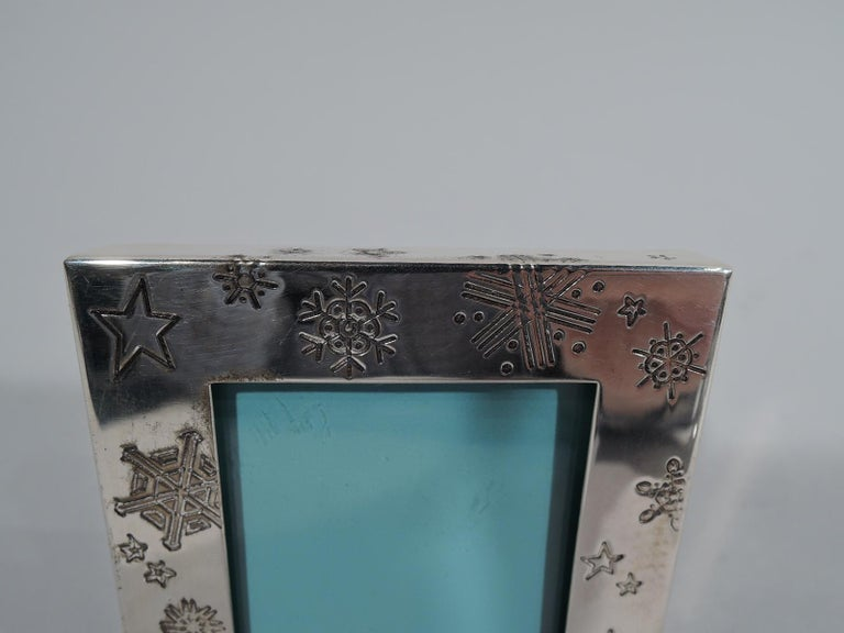 Winter wonderland sterling silver picture frame. Retailed by Tiffany & Co. in New York. Square window in flat surround with engraved (meteorological) snowflakes scattered on front and sides. With glass, eggshell blue liner, and black laminate back