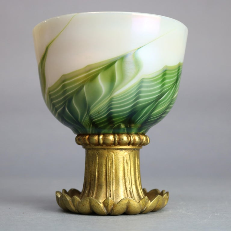An an antique Art Nouveau ceremonial chalice by Tiffany Studio offers Favrile art glass bowl having green, gold and white pulled feather design and gold interior, raised on gilt bronze foliate form base, maker signed and ambigram as photographed,
