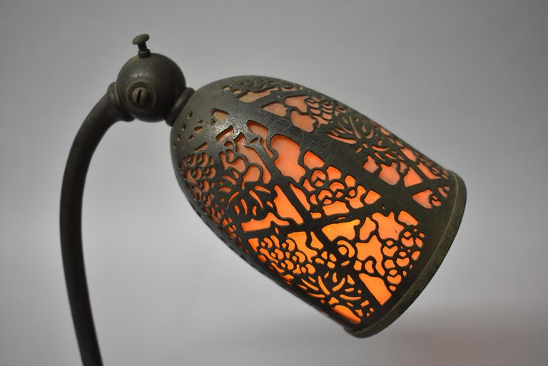 Antique Tiffany Studios bronze desk lamp with amber slag glass shade covered in filigree grapevine pattern. Single socket. Marked on the bottom #552. Shade adjusts.