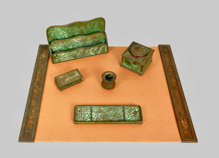 A 6 piece Tiffany Studios pine needle pattern fully signed bronze and glass desk set consisting of blotter ends, pen tray, inkwell, letter tray, nib cleaner and stamp box. The pine needle pattern was one the more popular of the Tiffany Studios'