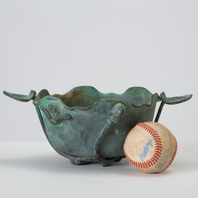 An irregular early 20th century bowl in heavy bronze with a fetching verdigris blue patina. The Art Nouveau design has scalloped and fluted edges, and the sides are decorated with lily pads and lotus blossoms, the stems of which extend underneath