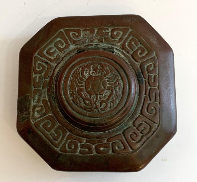 A wonderful Tiffany Studios bronze zodiac octagonal shaped inkwell with round lid that opens to a glass insert. It is decorated on a zodiac crab on the lid and is bordered with ancient zodiac symbols intertwined around the band. Stamped on the
