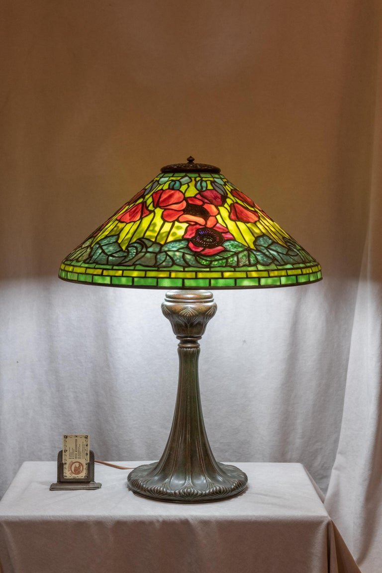 This spectacular lamp was one of Tiffany's best. The poppies are rich red with Fine Tiffany glass. The interior filagree metalwork behind the leaves give the appearance of veins to those leaves. The shade is remarkable condition. We had to hunt to