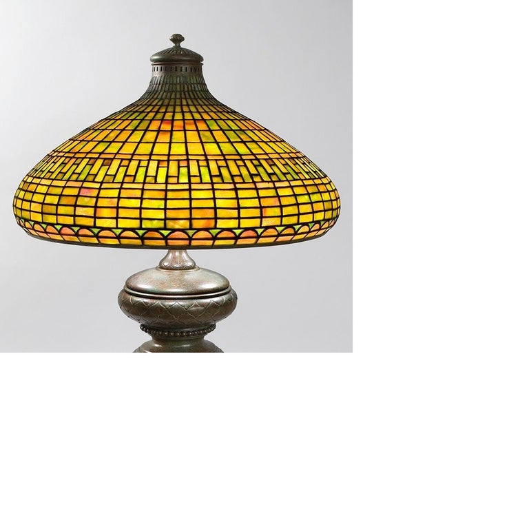 """A Tiffany Studios New York glass and bronze """"Geometric"""" table lamp, featuring a mottled orange, yellow and green leaded glass shade atop an intricately sculpted patinated bronze base.  Pictured in: Tiffany at Auction by Alastair Duncan, Rizzoli"""