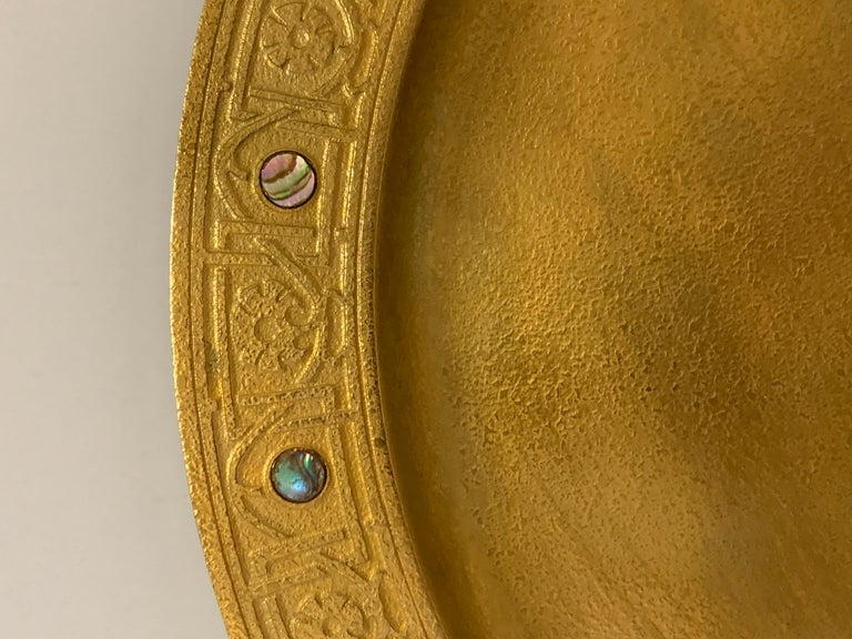 A signed Tiffany Studios gilt doré bronze charger inlaid on the rim with abalone insets. Features a nice rim design as well. Marked on the base with the number 1730. It is approx 12 inches in diameter. Overall good age appropriate condition with