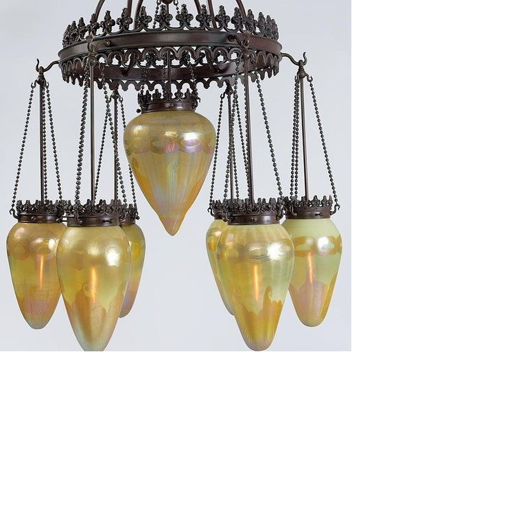 A Tiffany Studios New York golden stalactite chandelier with pulled gilt decoration, suspended from a patinated bronze and brass chain and pole system. This chandelier features a larger central stalactite surrounded by 6 smaller stalactites. The