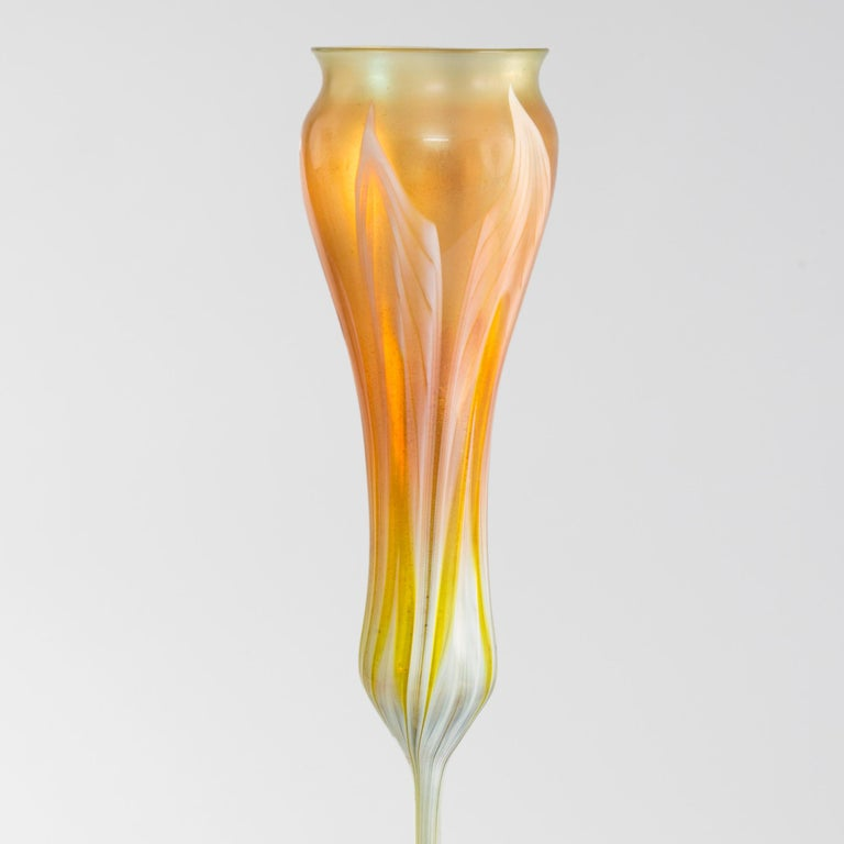 This Favrile glass flower form vase, by Tiffany Studios New York, is meant to suggest the calyx forms, open or closed, of crocus or tulip flowers. This richly-hued orange-yellow vase is tall and slender and colored with exquisite green and white