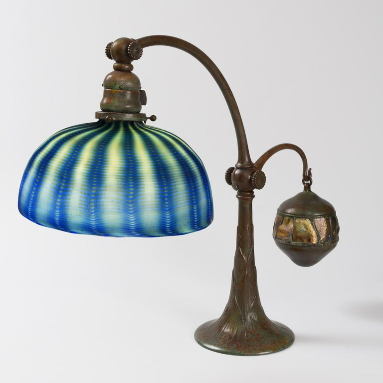 """A Tiffany Studios New York Favrile glass and patinated bronze desk lamp with an iridescent gold favrile glass """"Damascene"""" shade suspended from a patinated bronze """"Counterbalance"""" base, circa 1900.  A similar lamp is pictured in: Tiffany lamps and"""