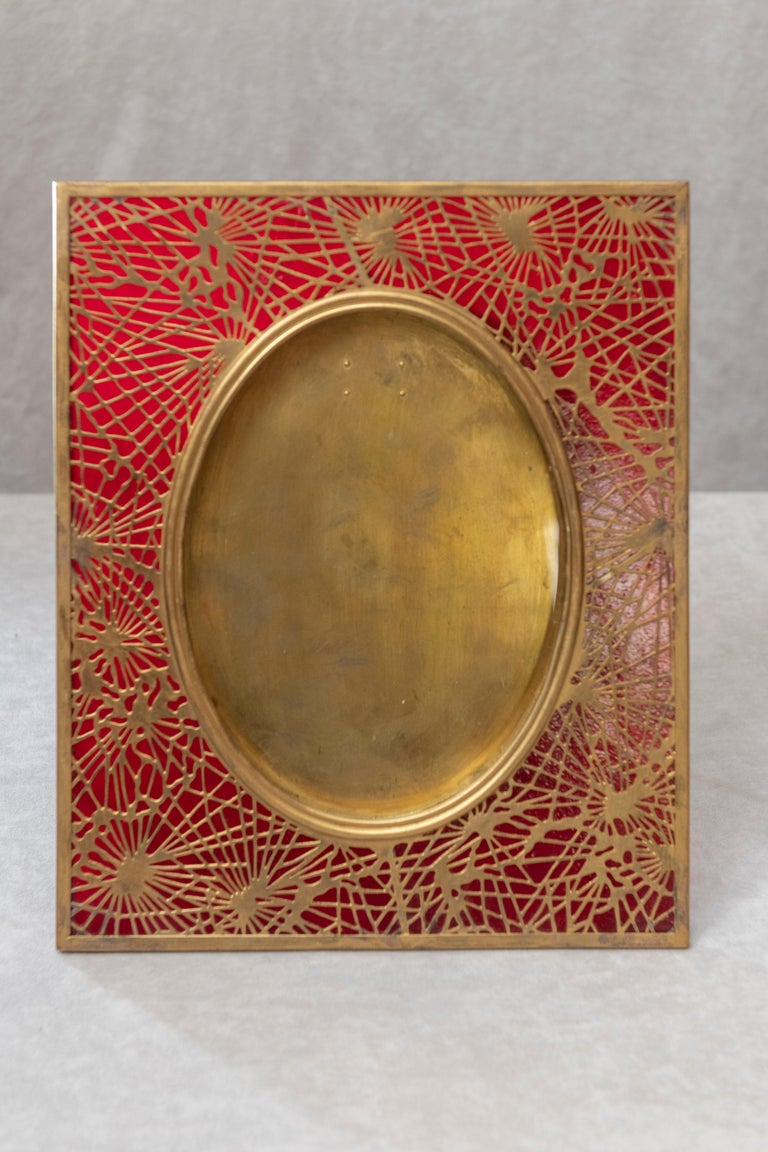 This beautiful original Tiffany Studios picture frame has ruby red glass and gilt metal, all done in their popular pine needle pattern. Normally the glass is green or amber. This one is rather exotic and has a rich look with the red background glass