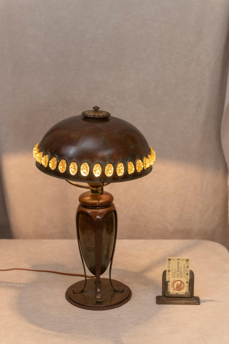 This very handsome lamp was done by the master lamp maker, Tiffany Studios. Rich brown patina and exotic jewels in the shade, and all in bronze make for a great package. An unusual and high quality lamp.