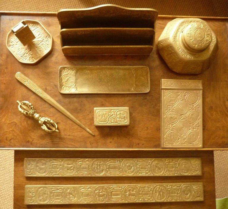 Late 19th-early 20th century Tiffany desk set consisting of a pen tray, pen rest, letter opener, paper rack, match stand, octagonal inkstand, memoranda pad, stamp box and large blotter ends. All are of bronze with gold finish, and are stamped with