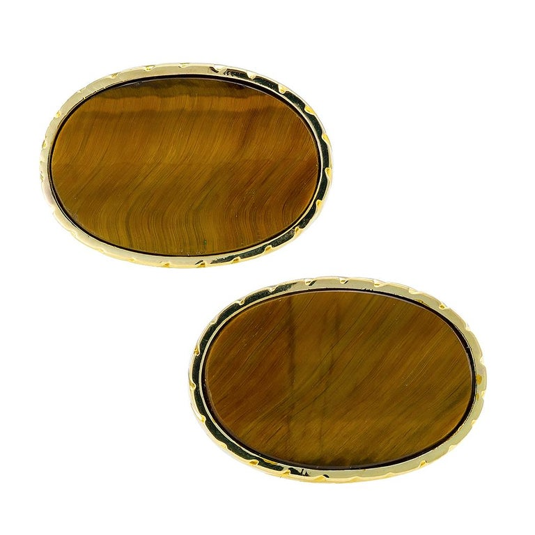 Tiger eye and gold cufflinks circa 1970. Featuring a pair of very distinctive, flat buff-top, oval tiger eye, set into conforming fluted bezels, to the back connectors inlaid with tiger eye, mounted in 14-karat yellow gold. We love the larger size