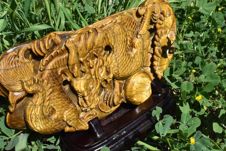 A stunning all natural genuine tiger's eye sculpture depicting a dragon chasing a ball. The sculpture is made with a whole slab of natural Tiger's Eye with fantastic iridescence. Fine carvings make the dragon come to life. Solid wood custom stand.