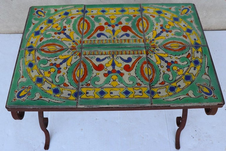 Chic wrought iron base, tile top garden or patio table, with six square tiles forming the rectangular top. The tiles are reminiscent of Catalina Pottery, the table is circa 1920s-1930s. Some of the grout which holds the tiles in place is missing,