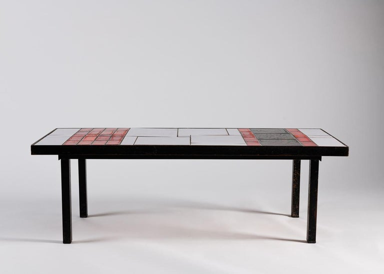 An elegant rectangular coffee table with a pared down dark metal frame and a tiled top arranged in a Mondrianesque pattern of black, red, and white rhombuses.