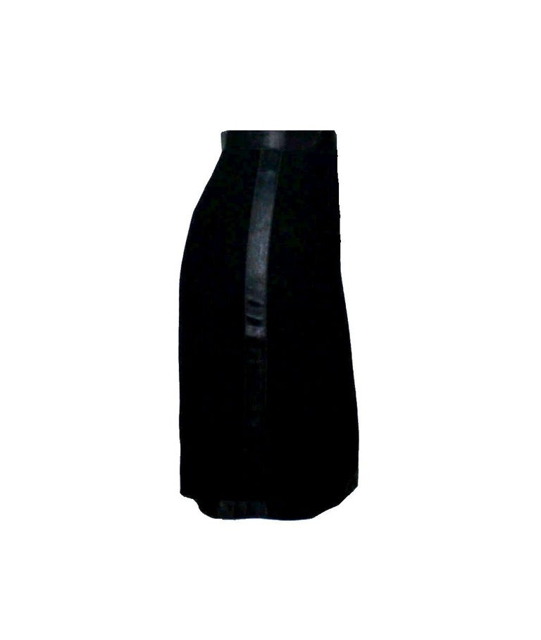 Beautiful CHANEL skirt designed by Karl Lagerfeld A true CHANEL signature item in the so famous black that will last you for many years Black fabric with satin strip trimming on hems and on sides - just like the skirt variation of a tuxedo Fully