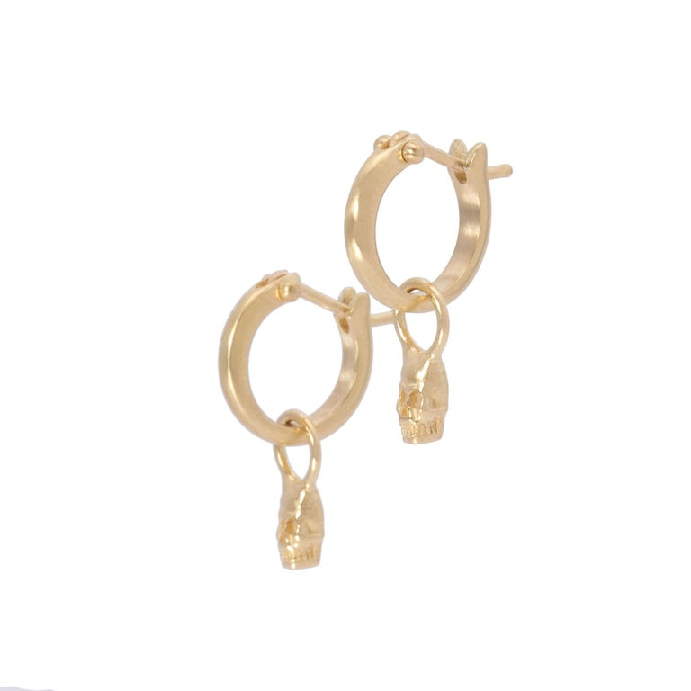 Tiny skulls hand crafted in 18k gold grin beneath small plain hoop earrings which click shut for security. As the symbol for both the past and the future, our ancestors and life, these tiny skull drop earrings in 18k gold are a whimsical nod to the