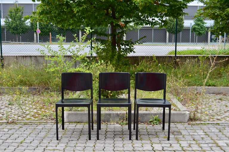 Tito Agnoli designed this dining chair for Matteo Grassi. It is made of black lacquered aluminium and black saddle leather. It is in vintage used condition. The edges has some wears and abrasions. Set of 3.