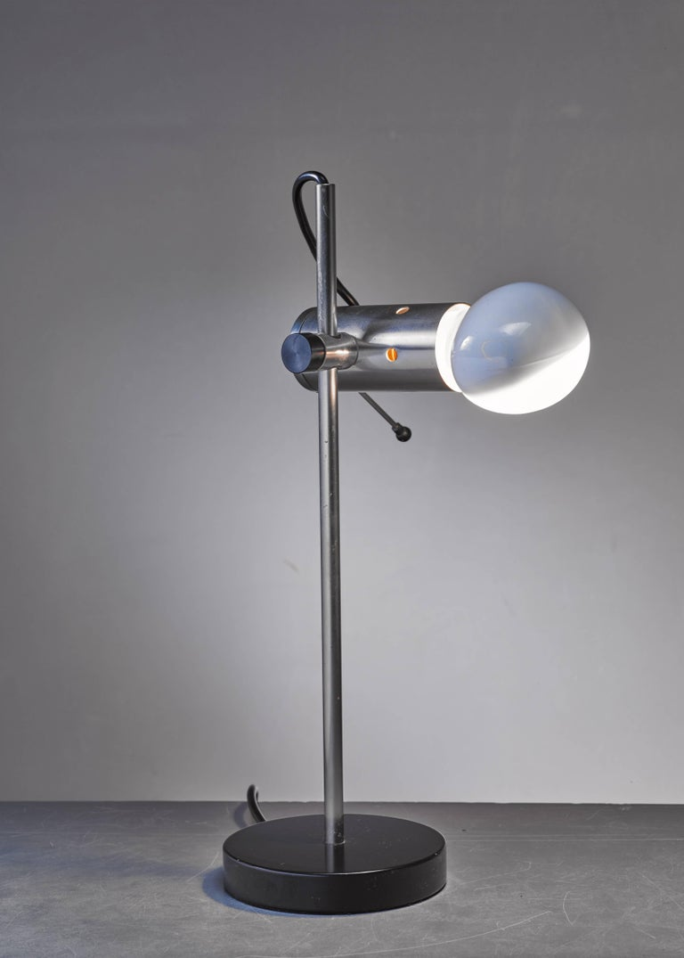 A metal model 251 table lamp by Tito Agnoli for O-Luce. The shade is height-adjustable and it can be turned around. The lamp has the original lightbulb.