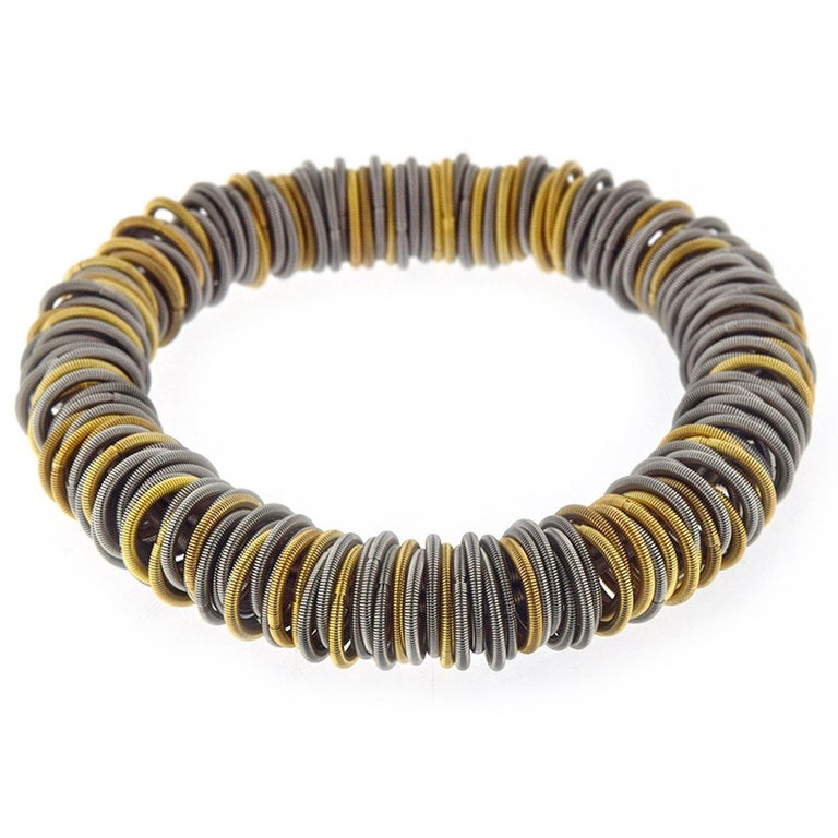 Balanced between the exotic and the industrial,  Tiziana Bra N1stainless steel and gold plated bracelet is strikingly elegant. The hardness of steel is softened by a clever structure of elastic hoops of finely spun springs, some plated with gold. By