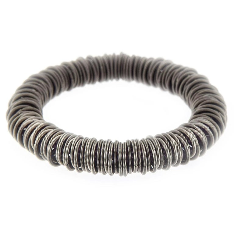 Balanced between the exotic and the industrial, the Tiziana N1 stainless steel Bangle Bracelet is strikingly elegant. The hardness of steel is softened by a clever structure of elastic hoops of finely spun springs. By transforming an otherwise