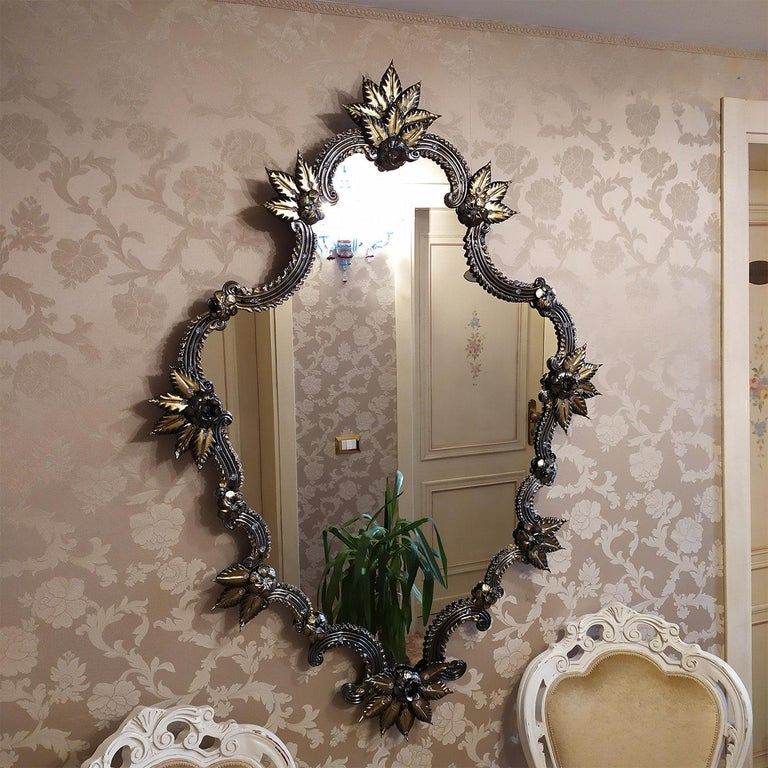 Exuding an opulent and dramatic allure, this wall mirror will make a singular and refined addition to an eclectic modern interior. A superb embodiment of the Venetian style and the valuable, long-lasting tradition of glassmaking, it is handmade of