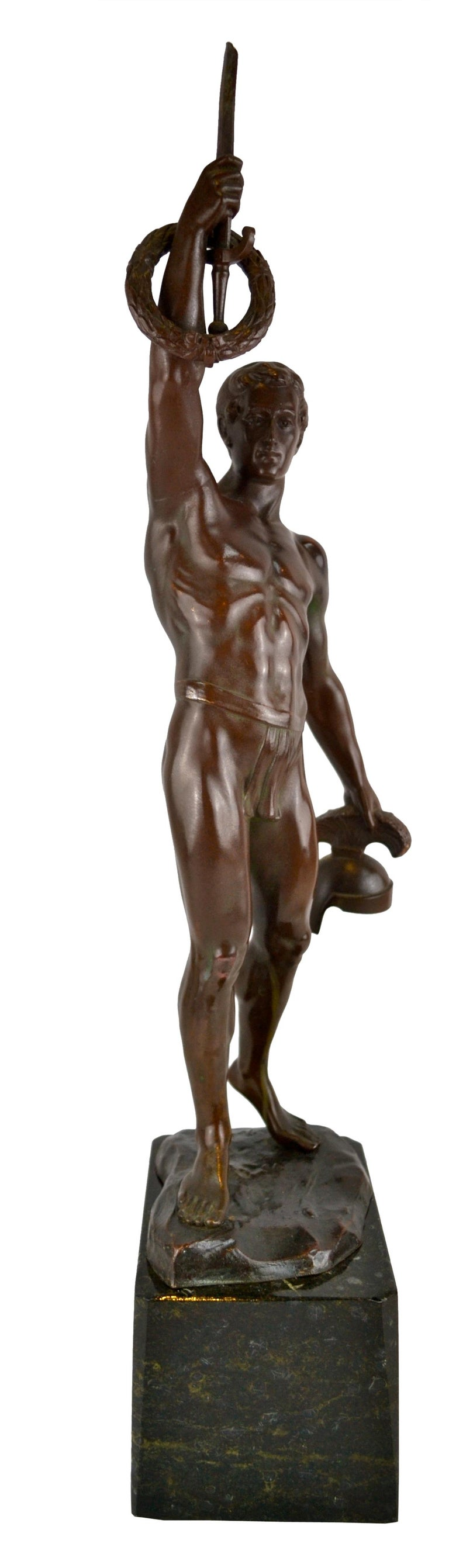 """A classical bronze statue of a muscular Olympic Greek fighting athlete titled """"To The Victor"""". The athlete has raised a hand holding a sword by its blade with a winner's laurel wreath around the hilt, and is holding his helmet in his other hand. The"""