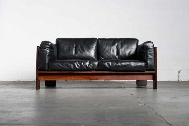 Highly sought after pair of black leather and Brazilian Rosewood 'Bastiano' loveseat sofas by Afra and Tobia Scarpa for Gavina, signed with several Gavina labels. This elegantly crafted sofa has been fabricated from Rosewood which displays a