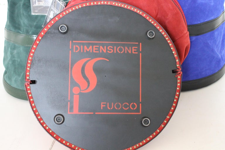 Dimensione Fuoco leather wood carrier designed by Tobia Scarpa, Italy, 2005.  These Minimalist showpieces combine tradition, functionality and brilliant craftsmanship and are a must have for every fireplace.  First quality red, green and blue