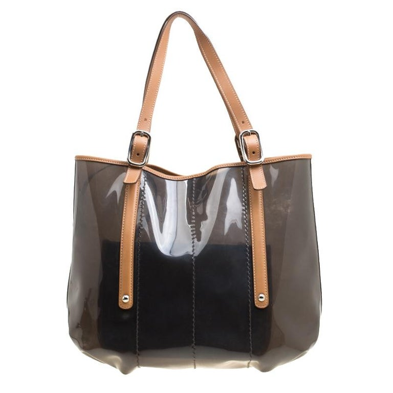 Meant for you to carry all your essentials with ease is this tote by Tod's. Crafted from PVC and leather trims, the bag is held by two buckle handles and accompanied by a pouch. It is complete with a spacious interior.  Includes: Original Dustbag