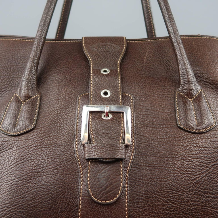 TOD'S weekender tote bag comes brown textured leather with double covered top handles, magnetic belt buckle top strap closure, and contrast stitch details throughout. Wear throughout. As-is.   Fair Pre-Owned Condition.   Measurements:   Length: