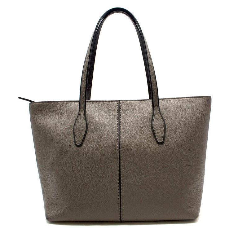 Tod's Joy Taupe Bag Large  -Grey large shopping tote -Two top handles -Silver tone tip closure -One main interior pocket -Two detachable pockets, one with slots and one with a zipped pocket -Comes with name tag and leather tassels  Please note,