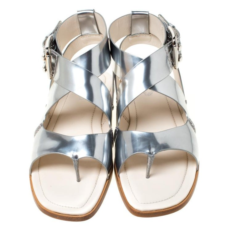 The sandals are designed for maximum comfort. They are by Tod's, crafted from metallic silver leather in a style of cross strap ankle fastening with buckle closure and leather insoles. This pair will accentuate and complement your outfit.  Includes: