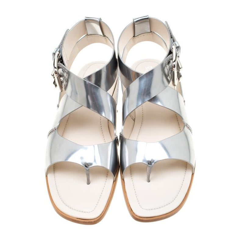 Flat sandals are a closet essential, and there's no reason why yours must be left behind. No better start than with these from Tod's! Crafted from metallic silver leather, they feature a simple design and ankle buckle straps.  Includes: Price Tag,