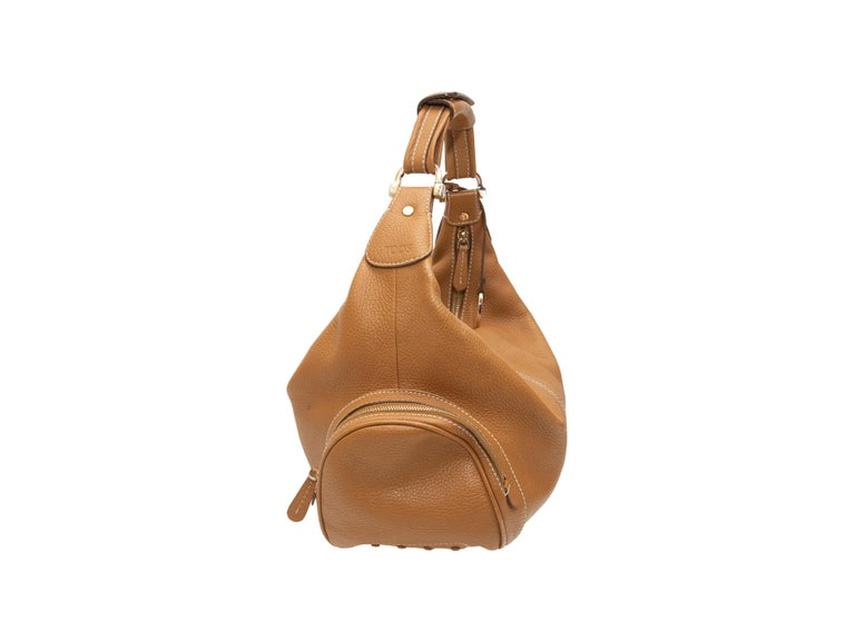Product details: Tan leather hobo shoulder bag by Tod's. Contrast stitching throughout. Silver-tone hardware. Dual exterior zip pockets. Zip closure at top. 11