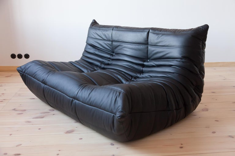 This Togo two-seat couch was designed by Michel Ducaroy in 1973 and was manufactured by Ligne Roset in France. It has been reupholstered in new black leather (131 x 102 x 70 cm). It has the original Ligne Roset logo and genuine Ligne Roset bottom.