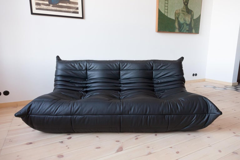 This Togo three-seat sofa was designed by Michel Ducaroy in 1973 and was manufactured by Ligne Roset in France. It has been reupholstered in new black leather (70 x 174 x 102 cm). It has the original Ligne Roset logo and genuine Ligne Roset bottom.