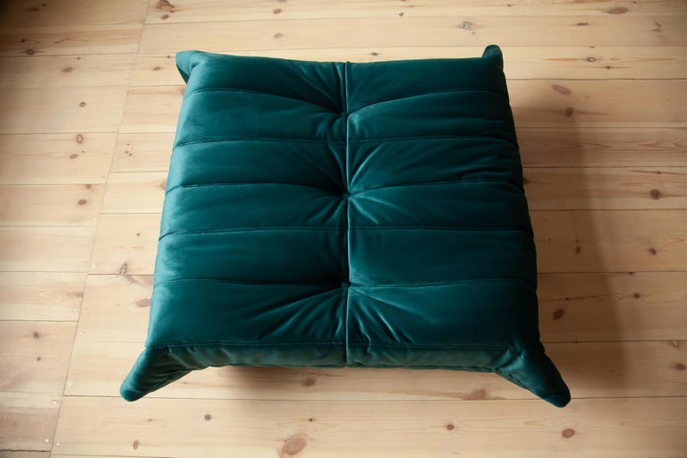 This Togo ottoman was designed by Michel Ducaroy in the 1973 and was manufactured by Ligne Roset in France. It has been reupholstered in new blue- green velvet (87 x 80 x 38 cm). It has the original Ligne Roset logo and genuine Ligne Roset bottom.