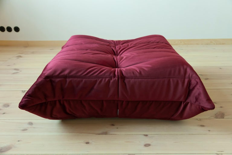 This Togo ottoman was designed by Michel Ducaroy in the 1970s and was manufactured by Ligne Roset in France. It has been reupholstered in new burgundy velvet (87 x 80 x 38 cm). It has the original Ligne Roset logo and genuine Ligne Roset bottom.